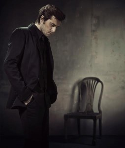 Handsome and calm man in a business suit on a dark background